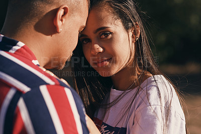 Buy stock photo Portrait of a young woman hugging her boyfriend outdoors