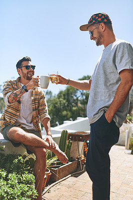 Buy stock photo Cropped shot of two cheerful young men enjoying a cup of coffee together outside on their balcony at home during the day