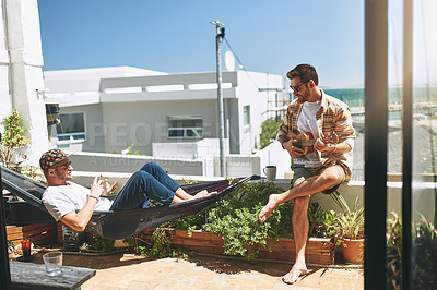 Buy stock photo Cropped shot of a cheerful young man playing on his guitar while his friend listens outside on a balcony during the day