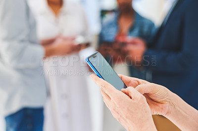 Buy stock photo Closeup shot of an unrecognisable businesswoman using a cellphone in an office with her colleagues in the background