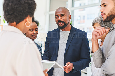 Buy stock photo Shot of a mature businessman having a discussion with his colleagues in an office