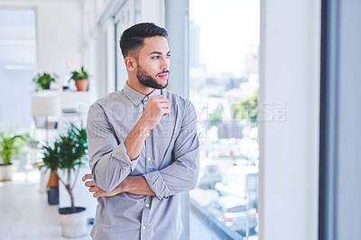 Buy stock photo Shot of a young businessman looking thoughtfully out the window in an office