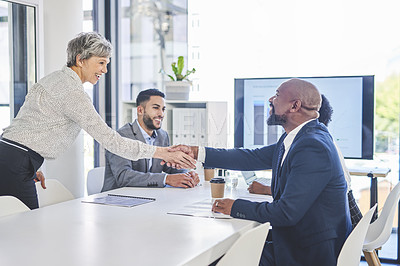 Buy stock photo Shot of two businesspeople shaking hands together during their meeting inside a boardroom