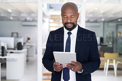 Buy stock photo Cropped shot of a handsome mature businessman using a digital tablet inside his office