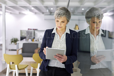 Buy stock photo Cropped shot of an attractive mature businesswoman using a digital tablet inside her office