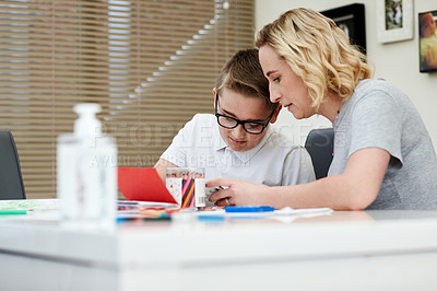 Buy stock photo Cropped shot of a mother assisting her young son with his homework at home
