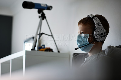 Buy stock photo Cropped shot of an adorable little boy wearing a surgical mask and headphones while busy gaming at home