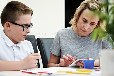Buy stock photo Cropped shot of a mother using a cellphone while assisting her young son with his homework at home