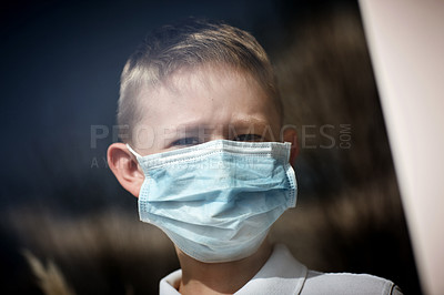 Buy stock photo Cropped shot of an adorable little boy wearing a surgical mask looking out of a window at home