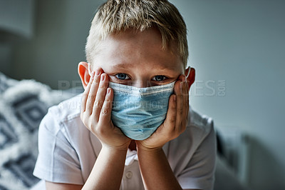 Buy stock photo Portrait of an adorable little boy wearing a surgical mask at home