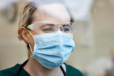 Buy stock photo Cropped shot of a female nurse wearing a surgical mask at a hospital
