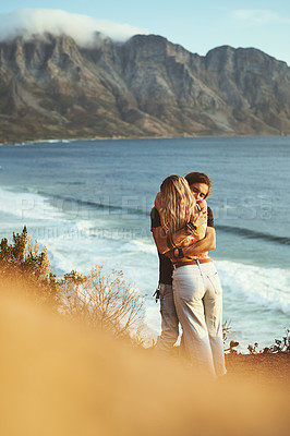 Buy stock photo Cropped shot of an affectionate young couple standing together and hugging on the mountainside near the sea