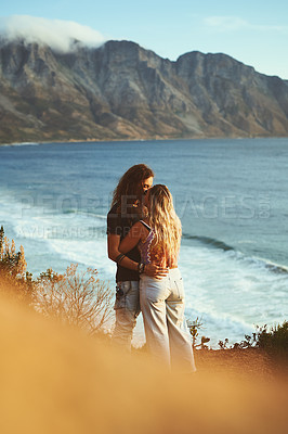Buy stock photo Cropped shot of an affectionate young couple standing together and kissing on the mountainside near the sea