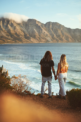 Buy stock photo Full length shot of an affectionate young couple standing together and looking out at sea during a day outdoors