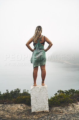 Buy stock photo Full length shot of an unrecognizable woman standing alone and looking out to sea during a day outdoors