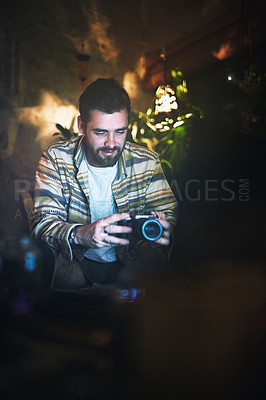 Buy stock photo Cropped shot of a handsome young man holding a camera while sitting indoors at home