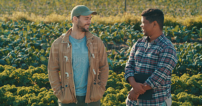Buy stock photo Cropped shot of two handsome young male farmers having a discussion while working together in a crop field