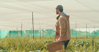 Buy stock photo Cropped shot of a handsome young male farmer working in a crop field during the day