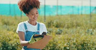 Buy stock photo Cropped shot of an attractive young female farmer writing on a clipboard while working in a crop field