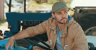 Buy stock photo Cropped shot of a handsome young male farmer looking thoughtful while driving a tractor in a farm house