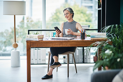 Buy stock photo Shot of a businesswoman having coffee while using her cellphone in her office