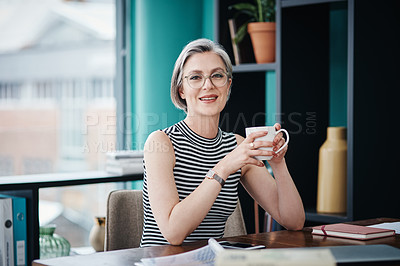 Buy stock photo Shot of a mature businesswoman having coffee in her office