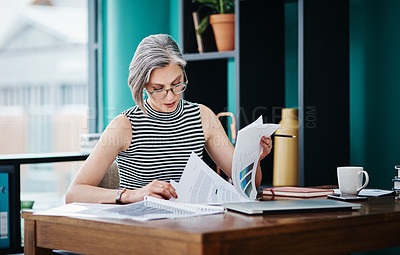 Buy stock photo Shot of of a mature businesswoman working on paperwork in her office