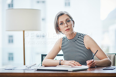 Buy stock photo Shot of of a mature businesswoman writing in her notebook