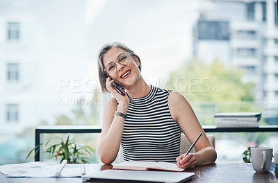 Buy stock photo Shot of a businesswoman making notes while talking on her cellphone