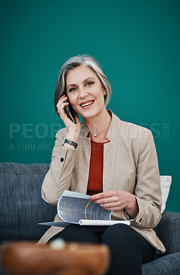 Buy stock photo Cropped portrait of an attractive mature businesswoman sitting alone and using her cellphone while reading paperwork in her home office