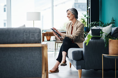 Buy stock photo Full length shot of an attractive mature businesswoman sitting alone and using a tablet in her home office