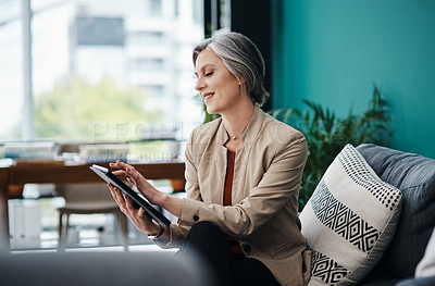 Buy stock photo Cropped shot of an attractive mature businesswoman sitting alone and using a tablet in her home office