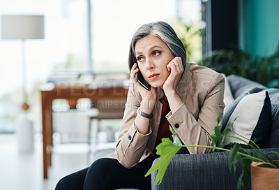 Buy stock photo Cropped shot of an attractive mature businesswoman sitting alone and talking on her cellphone in her home office
