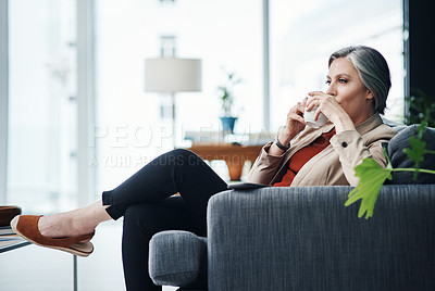 Buy stock photo Cropped shot of an attractive mature businesswoman sitting alone and enjoying a cup of coffee in her home office