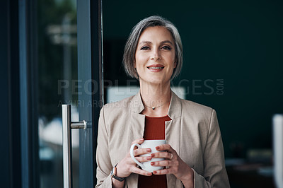 Buy stock photo Cropped portrait of an attractive mature businesswoman standing alone and enjoying a cup of coffee in her home office