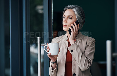 Buy stock photo Cropped shot of an attractive mature businesswoman standing alone and talking on her cellphone while enjoying a cup of coffee