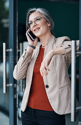Buy stock photo Cropped shot of an attractive mature businesswoman standing alone and talking on her cellphone in her home office