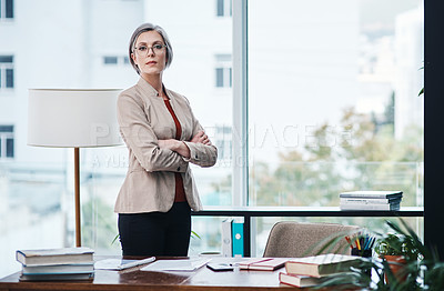 Buy stock photo Cropped portrait of an attractive mature businesswoman standing alone with her arms folded in her home office