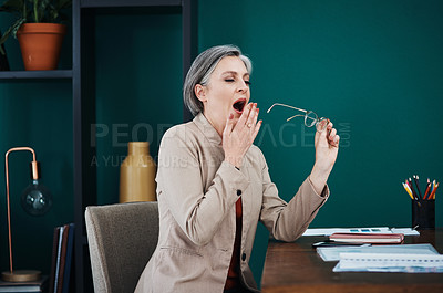 Buy stock photo Cropped shot of an attractive mature businesswoman sitting alone and yawning in her home office