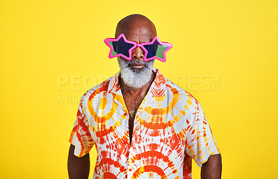 Buy stock photo Portrait of a funky and stylish senior man wearing sunglasses posing in studio against a yellow background