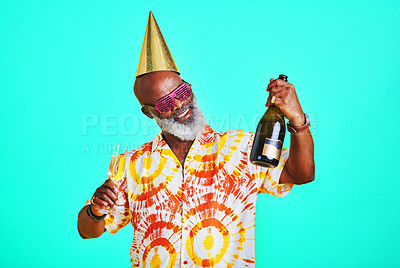 Buy stock photo Cropped shot of a funky and cheerful senior man celebrating and drinking champagne in studio against a turquoise background