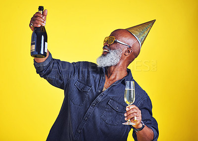Buy stock photo Cropped shot of a cheerful senior man celebrating and drinking champagne in studio against a yellow background