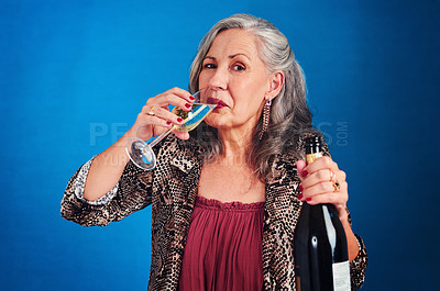 Buy stock photo Portrait of a funky and cheerful senior woman drinking champagne in studio against a blue background
