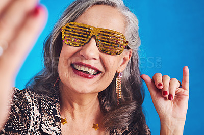 Buy stock photo Portrait of a funky and cheerful senior woman taking selfies against a blue background