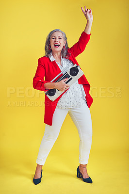 Buy stock photo Full length shot of a funky and stylish senior woman dancing while holding a boombox against a yellow background