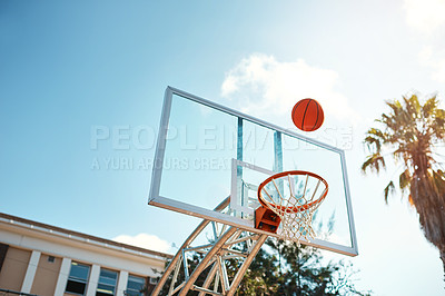 Buy stock photo Still life shot of a basketball landing into a net on a sports court