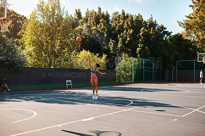 Buy stock photo Shot of a sporty young woman throwing a basketball into a net on a sports court