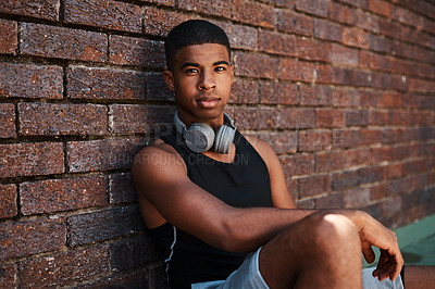 Buy stock photo Portrait of a sporty young man sitting against a wall outdoors
