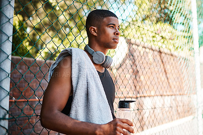 Buy stock photo Shot of a sporty young man taking a break while standing against a fence outdoors
