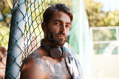 Buy stock photo Portrait of a sporty young man taking a break while standing against a fence outdoors